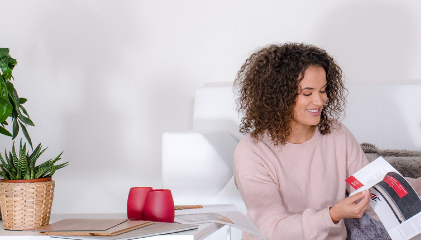 Woman reading an i4f brochure while smiling