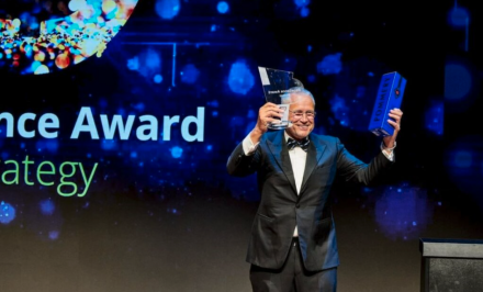 CEO holding an award and a bottle of champagne in a box on stage