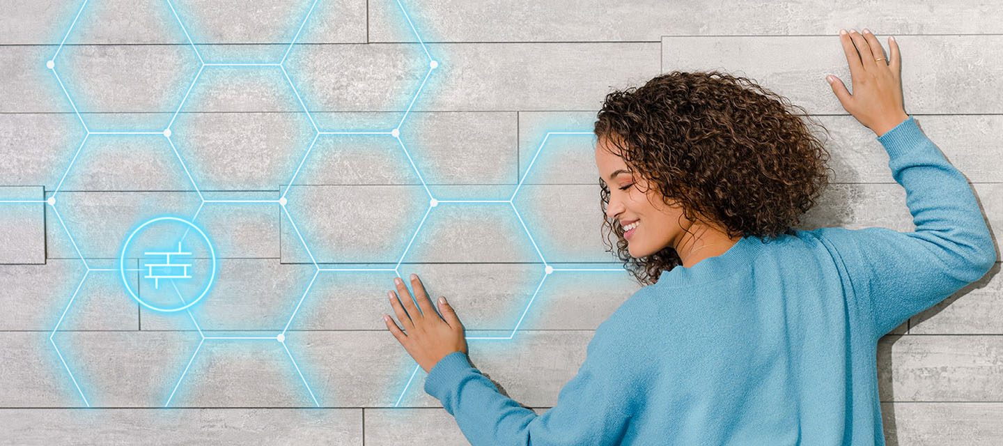 A woman with her head against a wall which has light blue pentagons highlighted